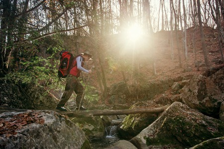 Adventure man hiking in woods with backpack, outdoor lifestyle