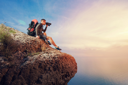 top mountain: A young man hiker  with a backpack hiking looking through binoculars sitting on a rock mountain over the sea.