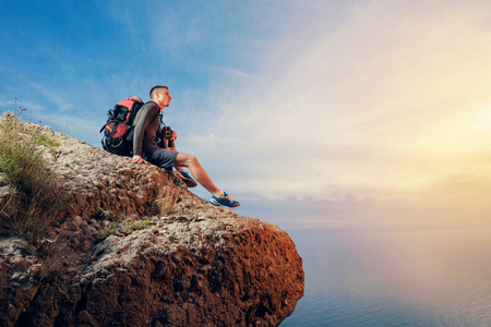 A young man hiker  with a backpack hiking looking through binoculars sitting on a rock mountain over the sea.