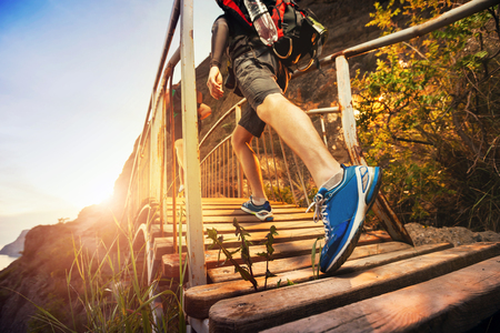 training shoes: Men are hiking in the mountains, walking on a wooden bridge at sunset. Healthy lifestyle. Stock Photo