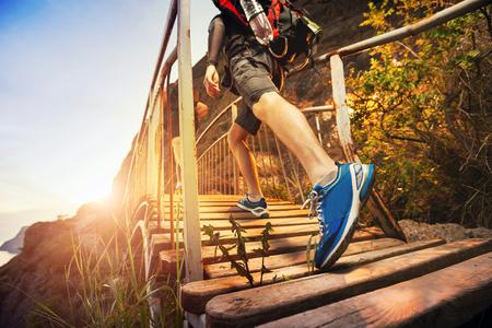 Os homens estão caminhando nas montanhas, caminhando sobre uma ponte de madeira no por do sol. Estilo de vida saudável.
