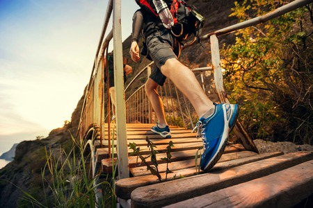 Men are hiking in the mountains, walking on a wooden bridge at sunset. Healthy lifestyle. Stock Photo