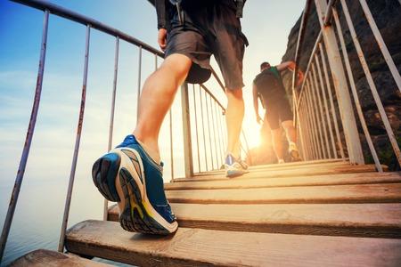 estilo de vida: Os homens estão caminhando nas montanhas, caminhando sobre uma ponte de madeira no por do sol. Estilo de vida saudável.