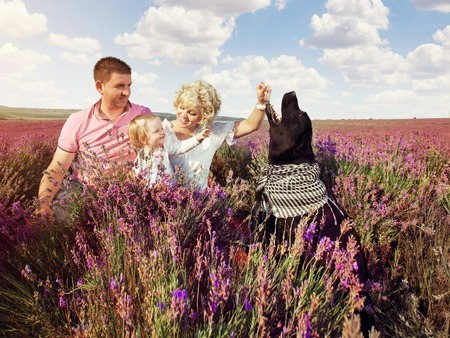 Family together in the lavender field. Portrait of a mother, father daughter and a dog sitting in the grass countryside. Stock Photo