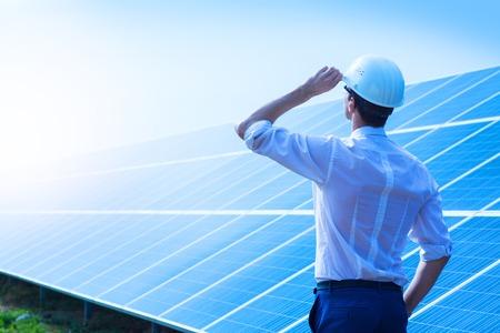 Zonne-energiecentrale. Man die zich dichtbij zonnepanelen. Duurzame energie. Stockfoto
