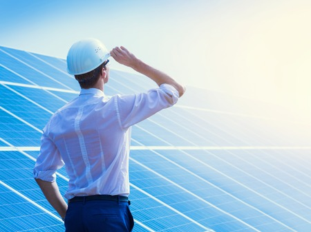Solar power plant. Man standing near solar panels. Renewable energy.