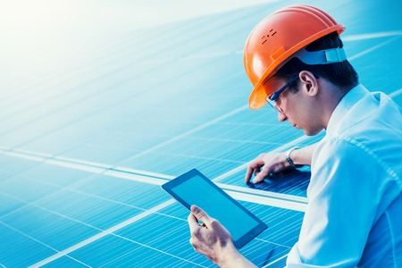 Engineer solar photovoltaic panels station checks with tablet computer. Stock Photo