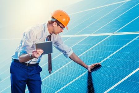 Engineer bij zonne-energiecentrale met zonnepanelen tablet controles. Stockfoto
