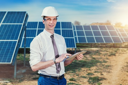 太陽光発電太陽電池パネル タブレットでエンジニアをチェックします。再生可能エネルギー発電の実践的なレッスン。