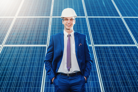 Portrait of a worker on a background of solar panels. Solar power plant. study of renewable energy power plants.