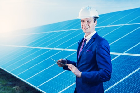 Solar panels. Engineer man with tablet on solar power station. Stock Photo
