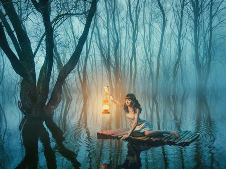 Sprookje vrouw met lantaarn drijvend op het meer in de mistige bos in rustieke witte jurk.