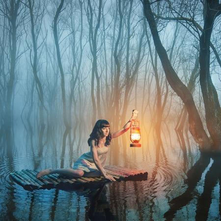 Vrouw met lantaarn drijvend op het meer in het mistige bos in rustieke witte jurk. Mooie sprookje. Stockfoto