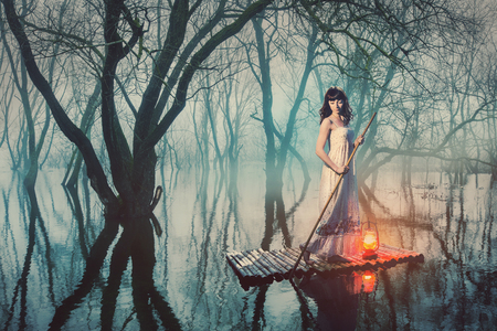 dream lake: Woman on a raft with a lantern floating on a pond in a misty forest. Fairy tale woman in a long dress.