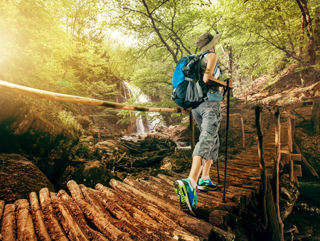 Hiking. Woman hikers walking on a bridge on the forest in the mountains on the waterfall. Girl with a backpack and sneakers traveling outdoors. Adventure in a hike. 写真素材