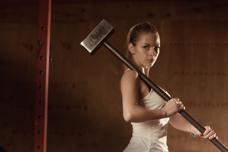 Fitness woman with a hammer in the gym. Portrait of attractive girl with a sledgehammer in training. Workout. Sports female.