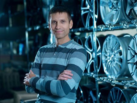 Man selling alloy wheel rims. Car wheels store. Portrait automobile dealer worker. Stock Photo