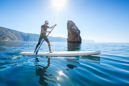 Stand up paddle boarding. Young man floating on a SUP board. The adventure of the sea with blue water on a surfing Фото со стока