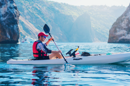 Kayaking. Man fisherman floats on a white kayak for fishing along the coast of the island near the rocks. Canoeing adventure on a calm sea with blue water. 스톡 콘텐츠