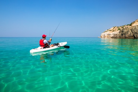 Man fishing on a kayak in the sea with clear turquoise water. Fisherman kayaking in the islands. Leisure activities on the ocean. 版權商用圖片