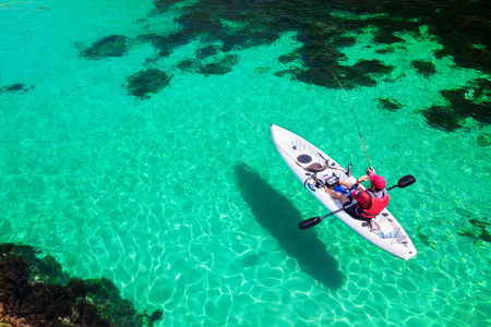 Man fishing on a kayak in the sea with clear turquoise water. Fisherman kayaking in the islands. Leisure activities on the ocean. Фото со стока