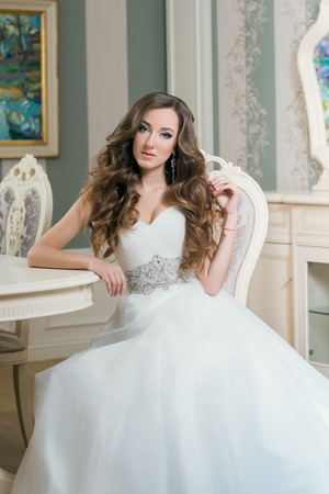 Bride in wedding dress sitting at a table in a luxurious room. Stock fotó