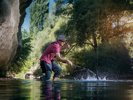 Fishing on the river. Fisherman catches a fish in forest. Man pulls a fish net. Stock Photo