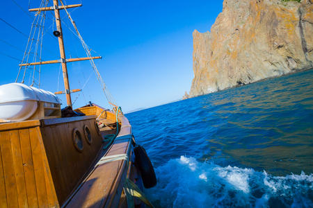 Wooden yacht. Vintage boat floating near the shore of a mountain. Stock fotó