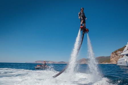 Silhouette of a fly board rider at sea. Water summer extreme sports.