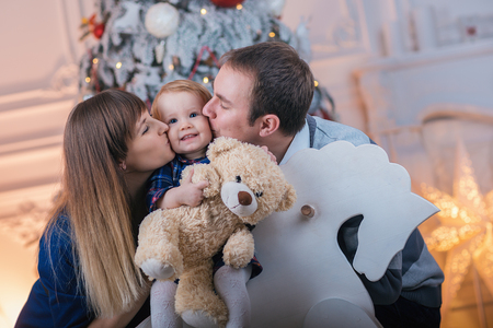 Happy family with a child spend Christmas together. Parents and daughter play at home near the Christmas tree. - Image