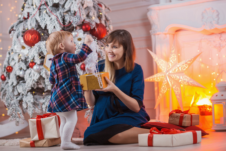 Child with mom with gifts near the Christmas tree. Mother and little daughter together with present indoors. New Years and Xmas holidays Stock Photo