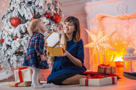 Child with mom with gifts near the Christmas tree. Mother and little daughter together with present indoors. New Years and Xmas holidays.