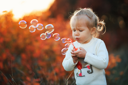 Little girl blowing soap bubbles in autumn park at sunset. Happy childhood concept. - Image