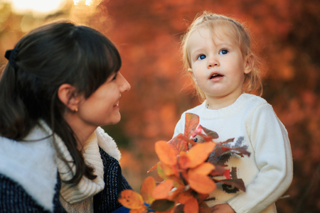 Mother and daughter with fallen leaves in autumn park. Little girl and her mom playing in the garden. - Image