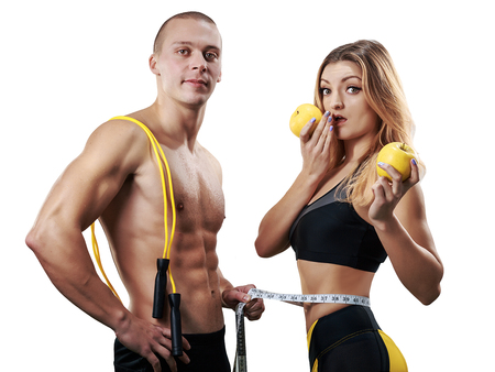 Athletic couple isolated. Muscular Man and Woman with measuring tape in gym. Weight loss, bodybuilding, sport and fitness, coach, workout, dieting and health. - Image Stock Photo