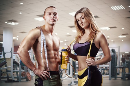 Athletic couple. Muscular Man and Woman with measuring tape in gym. Weight loss, bodybuilding, sport and fitness, coach, workout, dieting and health. - Image Stock Photo