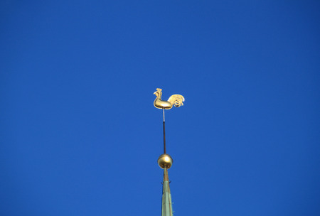 wind vane: RIGA, LATVIA - JANUARY 24, 2015: rooster weathervane on the spire of St. Peters Cathedral on January 24, 2015 in Riga.