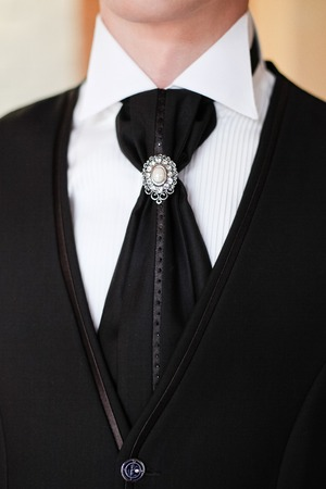 hand cuff: The groom in a white shirt with  black tie and vest