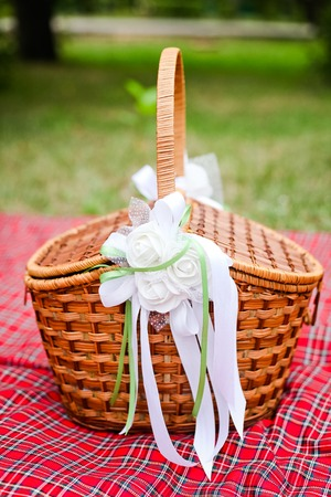 flower basket: Basket with white decorations on red plaid 1 Stock Photo