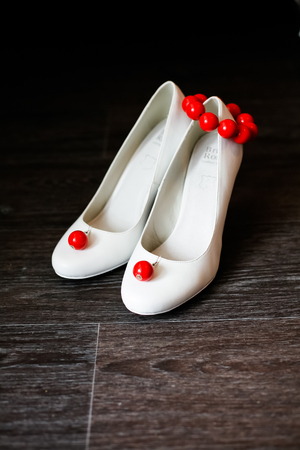 linoleum: Bridesmaid shoes white with red earrings and bracelet. Stock Photo