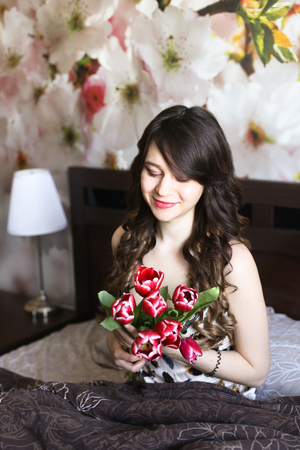 red bathrobe: Girl with red flowers in the bed 1 Stock Photo