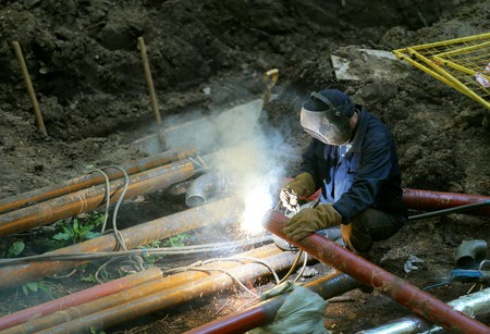 improvisation: Male welder worker wearing protective clothing fixing welding industrial construction water plumbing pipeline outside on site