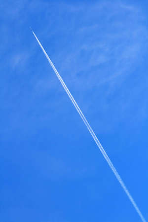 Photo of a airplane and inversion track in the blue sky Stock Photo