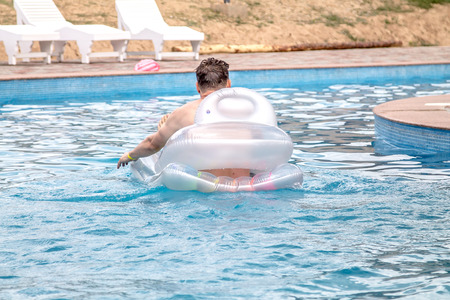 Man on the inflatable mattress in the pool