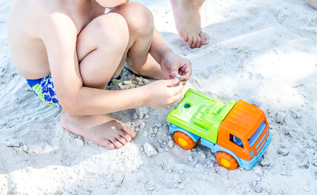 A child is playing on white sand in a sandbox on the beach