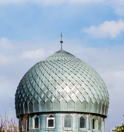 Dome of a mosque from galvanized metal on a sky background