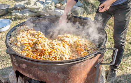 Preparation of pilaf in the fresh air Banco de Imagens