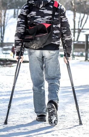 A man with crutches in winter