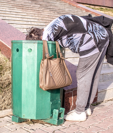 A homeless woman near a garbage can in the park
