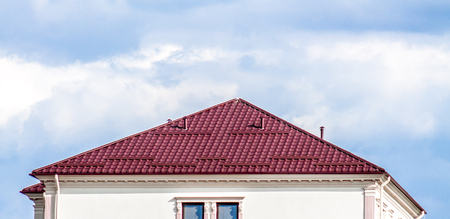 Roof of a house made of metal profile against a blue sky